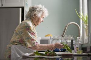 elderly woman washing produce