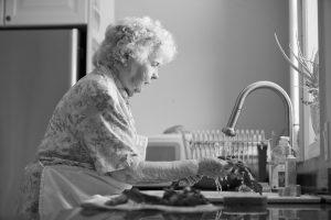 elderly woman washing produce BW